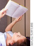Девушка лежит на спине и читает книгу (2014 год). Редакционное фото, фотограф Евгений Леонов / Фотобанк Лори