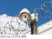 Круговая камера наружного видеонаблюдения в защитном кожухе на заборе с колючей проволокой на фоне облачного голубого неба (2012 год). Редакционное фото, фотограф Родион Власов / Фотобанк Лори