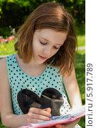 Девочка рисует карандашом в тетради в солнечный день. Стоковое фото, фотограф Елена Медведева / Фотобанк Лори