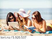 Купить «Девушки отдыхают у моря на пляже с планшетным компьютером и книгой», фото № 5920537, снято 11 июля 2013 г. (c) Syda Productions / Фотобанк Лори