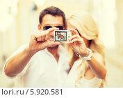 Купить «Молодая пара фотографирует себя на улице», фото № 5920581, снято 14 июля 2013 г. (c) Syda Productions / Фотобанк Лори