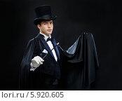 Купить «Фокусник в черной шляпе и черной одежде держит в руках палочку», фото № 5920605, снято 12 сентября 2013 г. (c) Syda Productions / Фотобанк Лори