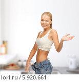 Купить «Девушка в больших джинсах улыбается на кухне», фото № 5920661, снято 23 марта 2013 г. (c) Syda Productions / Фотобанк Лори