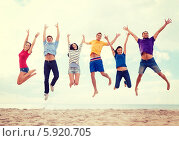 Купить «Друзья одновременно прыгают от радости на морском берегу, подняв руки вверх», фото № 5920705, снято 31 августа 2013 г. (c) Syda Productions / Фотобанк Лори