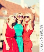 Купить «Три веселые подруги фотографируют себя, путешествуя по городу», фото № 5920789, снято 8 сентября 2013 г. (c) Syda Productions / Фотобанк Лори
