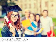 Купить «Радостная девушка в очках и в шляпе выпускника держит в руках диплом, перевязанный красной лентой», фото № 5921037, снято 15 сентября 2013 г. (c) Syda Productions / Фотобанк Лори
