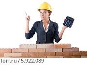 Купить «Деловая женщина в жёлтой строительной каске с калькулятором стоит у кирпичной стены», фото № 5922089, снято 27 июля 2012 г. (c) Elnur / Фотобанк Лори