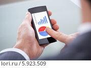 Купить «бизнесмен смотрит статистику на телефоне», фото № 5923509, снято 29 декабря 2013 г. (c) Андрей Попов / Фотобанк Лори