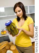 Купить «Девушка на кухне держит банку соленых огурцов», фото № 5924445, снято 23 апреля 2019 г. (c) BE&W Photo / Фотобанк Лори