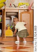 Купить «Девочка заглядывает в шкаф под раковиной на кухне», фото № 5924869, снято 29 января 2020 г. (c) BE&W Photo / Фотобанк Лори