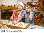 Купить «Дети вырезают из теста печенье формочками, готовя угощение к Рождеству», фото № 5925489, снято 23 марта 2019 г. (c) BE&W Photo / Фотобанк Лори