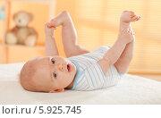 Купить «Младенец лежит на пеленальном столе, задрав ноги», фото № 5925745, снято 13 декабря 2017 г. (c) Joanna Malesa / Фотобанк Лори