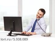 Купить «Улыбающийся бизнесмен в офисе печатает на компьютере и одновременно разговаривает по телефону», фото № 5938089, снято 15 марта 2014 г. (c) Syda Productions / Фотобанк Лори