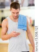 Молодой мужчина с полотенцем на плече ислушает музыку через наушники смартфона после занятий фитнесом. Стоковое фото, фотограф Syda Productions / Фотобанк Лори