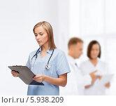 Купить «Серьезная женщина-врач со стетоскопом и клипбордом в руках на фоне своих коллег», фото № 5938209, снято 5 декабря 2013 г. (c) Syda Productions / Фотобанк Лори