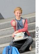 Купить «Успешный первокурсник с учебниками и ноутбуком поднял вверх большой палец в знак одобрения, сидя на университетской лестнице», фото № 5943429, снято 8 мая 2014 г. (c) CandyBox Images / Фотобанк Лори