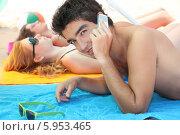 молодой человек лежит на пляже и говорит по телефону. Стоковое фото, фотограф Phovoir Images / Фотобанк Лори