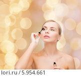 Купить «Красивая женщина красит ресницы тушью с помощью кисточки на праздничном фоне», фото № 5954661, снято 5 декабря 2013 г. (c) Syda Productions / Фотобанк Лори