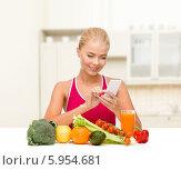 Купить «Молодая женщина считает калории, сидя за столом с овощами и фруктами», фото № 5954681, снято 23 марта 2013 г. (c) Syda Productions / Фотобанк Лори