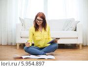 Купить «Привлекательная девушка в желтой блузке и очках сидит на полу в комнате рядом с белым диваном и готовится к экзаменам», фото № 5954897, снято 19 марта 2014 г. (c) Syda Productions / Фотобанк Лори
