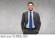 Купить «Позитивный бизнесмен в расстегнутом пиджаке стоит, засунув руки в карманы брюк, на фоне серой бетонной стены», фото № 5955181, снято 19 июля 2018 г. (c) Syda Productions / Фотобанк Лори