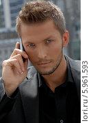 Серьезный молодой мужчина с мобильным телефоном. Стоковое фото, агентство BE&W Photo / Фотобанк Лори