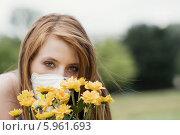 Купить «Красивая рыжая девушка в защитной маске с букетом цветов. Аллергия», фото № 5961693, снято 19 марта 2019 г. (c) BE&W Photo / Фотобанк Лори