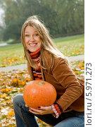 Купить «Веселая девушка с ослепительной улыбкой и с оранжевой тыквой в руках», фото № 5971273, снято 24 августа 2019 г. (c) BE&W Photo / Фотобанк Лори