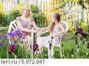 Купить «Мама с дочкой отдыхают на даче среди цветов», фото № 5972041, снято 24 мая 2014 г. (c) Майя Крученкова / Фотобанк Лори