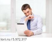 Купить «Молодой бизнесмен задумавшись смотрит на экран планшетного компьютера», фото № 5972317, снято 15 марта 2014 г. (c) Syda Productions / Фотобанк Лори