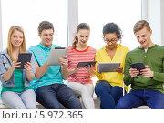 Купить «Счастливые молодые люди с планшетными компьютерами улыбаются, читая новости», фото № 5972365, снято 29 марта 2014 г. (c) Syda Productions / Фотобанк Лори