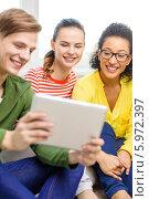 Молодой человек и две девушки улыбаясь рассматривают картинки на экране планшетного компьютера. Стоковое фото, фотограф Syda Productions / Фотобанк Лори