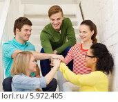 Купить «Молодые люди сложили руки вместе, сидя на лестнице», фото № 5972405, снято 29 марта 2014 г. (c) Syda Productions / Фотобанк Лори