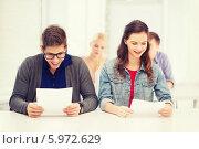 Купить «Молодой человек и девушка с тестовыми заданиями сидят в аудитории», фото № 5972629, снято 2 ноября 2013 г. (c) Syda Productions / Фотобанк Лори