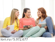 Купить «Веселые подруги смеются, сидя на диване с планшетными компьютерами», фото № 5972677, снято 12 апреля 2014 г. (c) Syda Productions / Фотобанк Лори