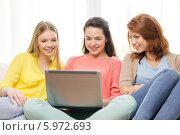 Три счастливые подруги рассматривают что-то на экране ноутбука, сидя дома на диване. Стоковое фото, фотограф Syda Productions / Фотобанк Лори
