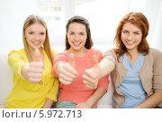 Купить «Три обаятельные подруги с улыбкой показывают жест одобрения, сидя на диване дома», фото № 5972713, снято 12 апреля 2014 г. (c) Syda Productions / Фотобанк Лори
