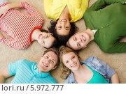 Счастливые друзья лежат на полу, соприкоснувшись головами. Стоковое фото, фотограф Syda Productions / Фотобанк Лори