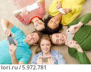 Купить «Друзья со смартфонами лежат на полу, соприкоснувшись головами», фото № 5972781, снято 29 марта 2014 г. (c) Syda Productions / Фотобанк Лори