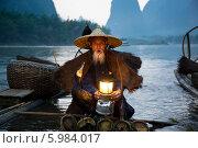 Старый китаец разжигает лампу для ночной рыбалки с ручными бакланами на фоне гор в провинции Гуанси (2013 год). Редакционное фото, фотограф Николай Винокуров / Фотобанк Лори