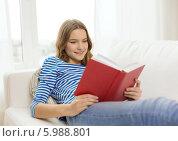 Купить «Девушка с интересом читает книгу», фото № 5988801, снято 26 февраля 2014 г. (c) Syda Productions / Фотобанк Лори