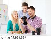 Купить «Молодые сотрудники в офисе просматривают фотографии на дисплее фотокамеры», фото № 5988889, снято 17 мая 2014 г. (c) Syda Productions / Фотобанк Лори