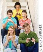 Купить «Группа тинейджеров со смартфонами в руках сидит на лестнице», фото № 5988913, снято 29 марта 2014 г. (c) Syda Productions / Фотобанк Лори
