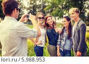 Молодой человек в парке фотографирует своих друзей. Стоковое фото, фотограф Syda Productions / Фотобанк Лори