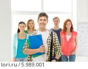 Купить «Молодой человек стоит впереди своих друзей с папками в руках и сумкой для ноутбука», фото № 5989001, снято 4 мая 2014 г. (c) Syda Productions / Фотобанк Лори