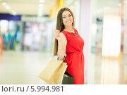 Красивая девушка с длинными волосами в красном платье делает покупки, держит пакеты. Стоковое фото, фотограф Вера Франц / Фотобанк Лори