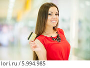 Купить «Красивая девушка с длинными волосами в красном платье делает покупки, держит кредитную карту», фото № 5994985, снято 10 июня 2014 г. (c) Вера Франц / Фотобанк Лори