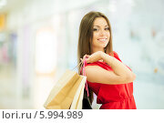 Купить «Красивая девушка с длинными волосами в красном платье делает покупки, держит пакеты», фото № 5994989, снято 10 июня 2014 г. (c) Вера Франц / Фотобанк Лори