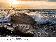 Волна разбивается о прибрежный камень на закате. Каякер гребет в бушующем море. Стоковое фото, фотограф Алексей Попов / Фотобанк Лори
