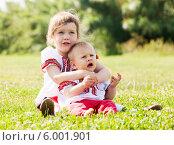 Купить «Двое детей в традиционной русской одежде сидят на зеленой лужайке», фото № 6001901, снято 15 июня 2013 г. (c) Яков Филимонов / Фотобанк Лори